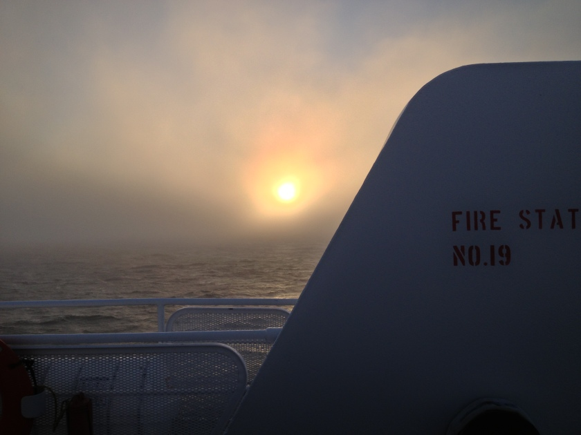 The setting sun through the fog - heading home onboard the MV Coho